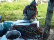 Yupiq woman preparing smoked king salmon strips for storage